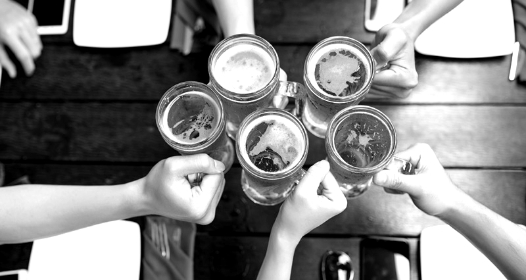 Five people holding beer glasses press their glasses together in a cheer.