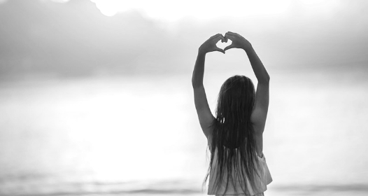 A girl with long hair holds her arms above her head, making a heart shape with her hands.